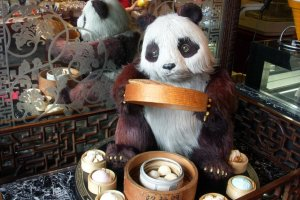 一個捧著蒸籠的卡通熊貓迎接著前來的顧客