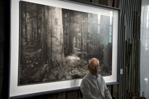 Hiroshi Sugimoto parado frente a una de sus imágenes
