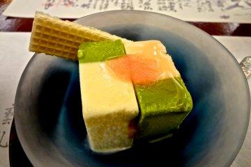 <p>ไอศกรีมกับเมนูที่เขียนด้วยลายมืออยู่ข้างหลัง</p>