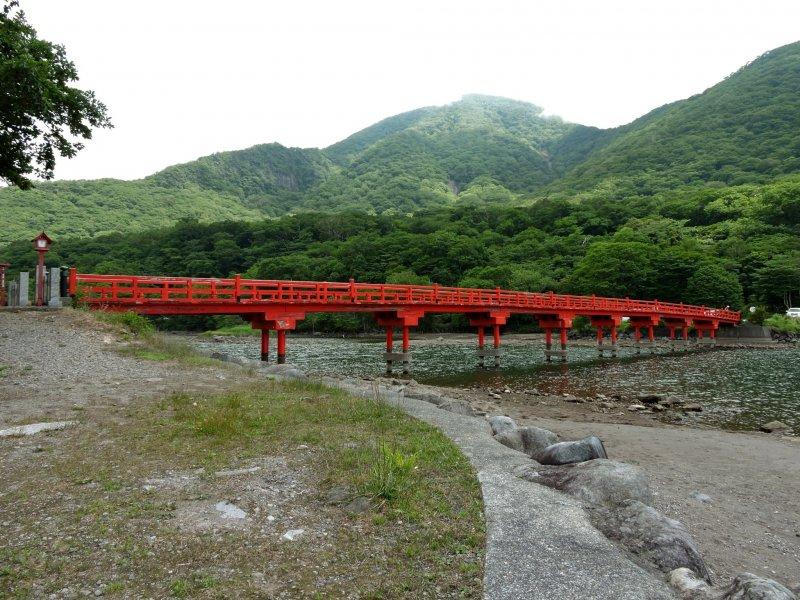 A red bridge crosses a corner of the lake