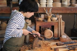 Creating her own wooden pot