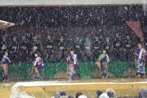 The stage is outside at a shrine. Audience members must also endure the cold weather.