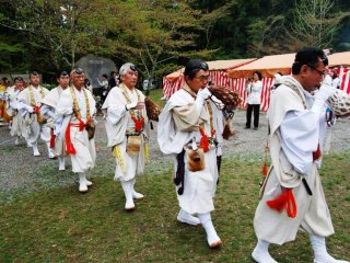 In formation, blowing the conch shell, yamabushi are entering the sacred bonfire place