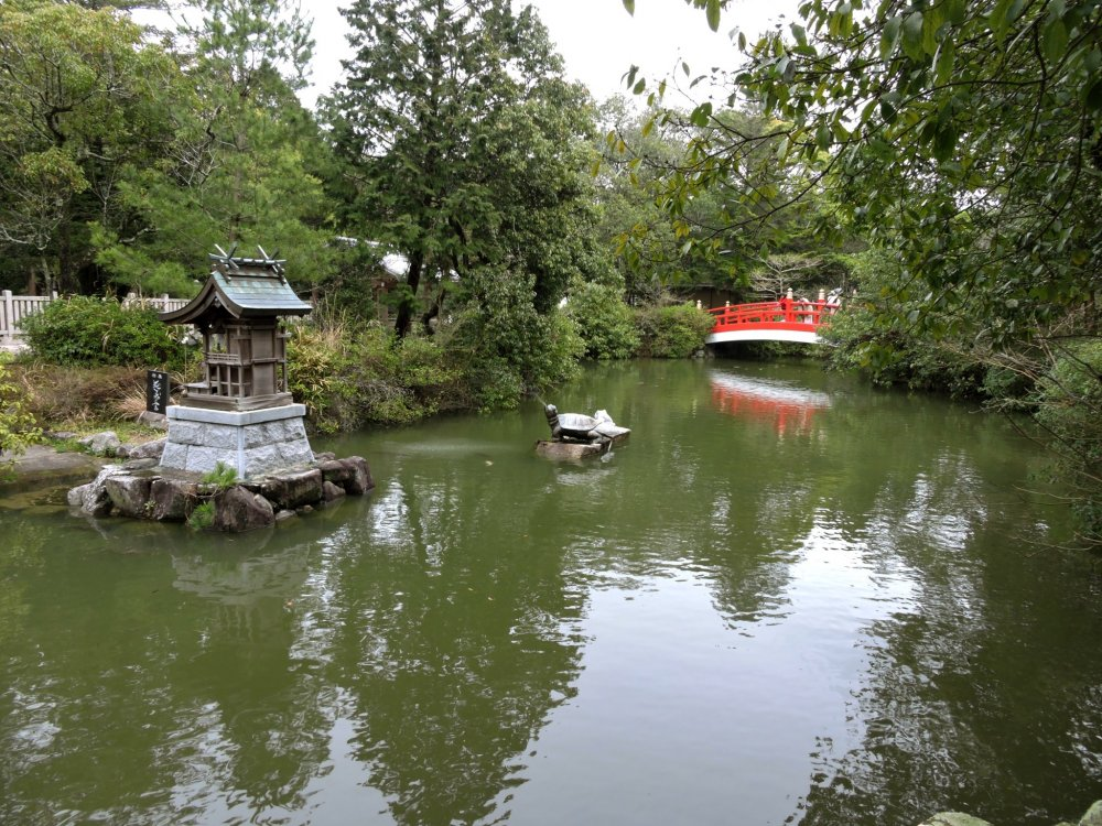 Pond with red bridge, stone turtle and small island shrine