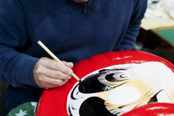 다루마 인형 위 눈썹을 그리다