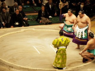 The Yokozuna (top ranker wrestler) champion makes a ceremonious entrance into the ring, flanked by two makuuchi wrestlers