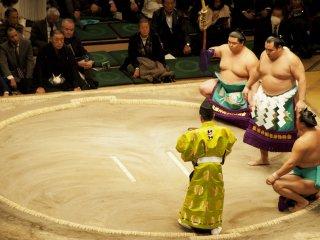 Võ sĩ yokozuna cao cấp thực hiện nghi lễ khi vào vòng đấu, hai bên là hai makuuchi