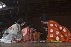 These ladies in court costumes playing karuta which is an ancient card game which have to match two halves of a poem