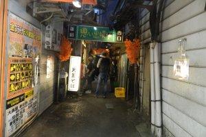 "That sign says ""Omoide Yokocho"" in Japanese"