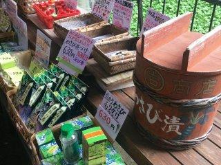 มีสินค้าวาซาบิหลากหลายให้เลือกซื้อ ต้นวาซาบิสีเขียวสดอยู่ข้างหลัง