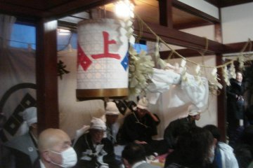 The men of the house where this year's performance takes place are in the back of the room; in front is a lantern with the symbol of the Kami-za, one of Kurokawa's two Noh troupes