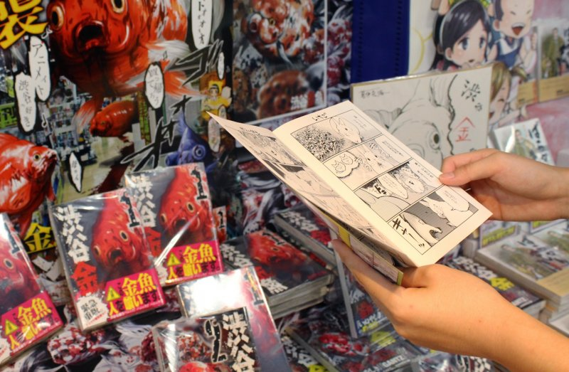 Read a manga about a rabbit in front of a display about murderous fish