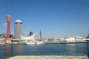"""Panorama do porto de Kobe, com a sua inconfundível torre vermelha. Esta torre, com 108 metros de altura e um formato que reproduz (livremente) o tambor tradicional japonês """"taiko"""", foi construída em 1963 como um miradouro e estrutura de embelezamento do porto. Ao final do dia enche-se de luzes."""