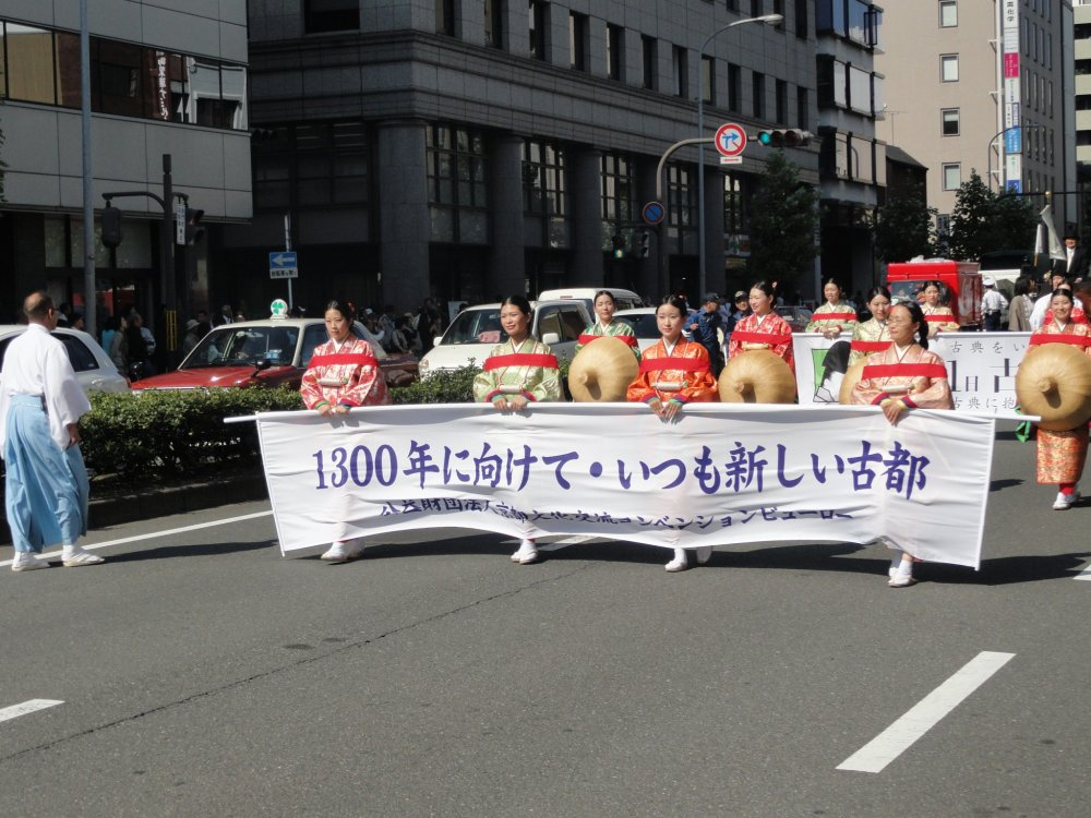 A história do Japão começa a desfilar à sua frente. Antes de cada conjunto de figurantes vem um grupo com a indicação da era histórica a que corresponde