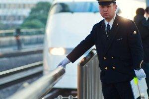 Un conductor de Japan Railways checando las vías mientras el Shinkansen Tokaido de Kioto y Shin Osaka llega a Tokio