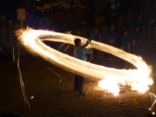 A festival participant swings a fiery torch at the annual Hifuri Shinji at Aso Shrine