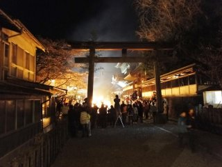 The torii gate of Aso Shrine lit up by the fire's glow