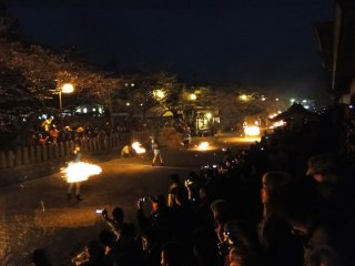 A host of fiery torches on the path in front of Aso Shrine