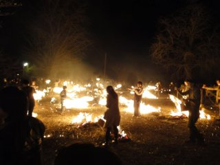 Audience members swing torches in a nearby field