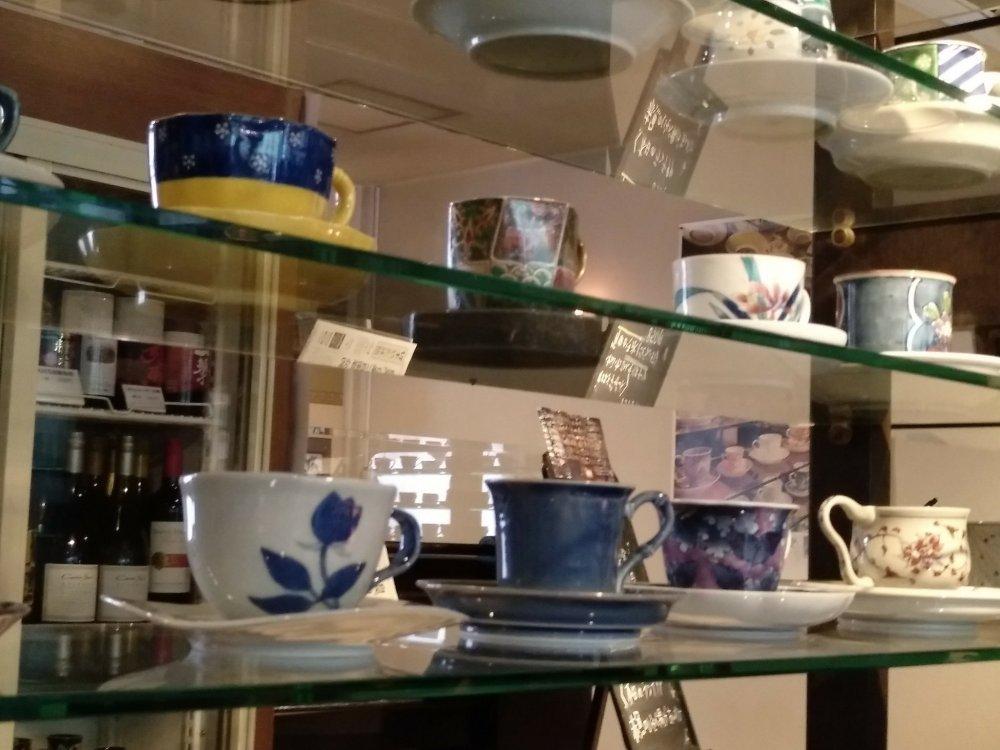 """O café e restaurante """"Galeria Arita"""" é um estabelecimento que, para além de comida deliciosa, expõe uma impressionante coleção de chávenas criadas em Arita, as quais reproduzem exemplares históricos e passam por todos os estilos e períodos. Este estabelecimento fica muito próximo do Museu Prefeitural de Cerâmica de Kyushu, e tem estacionamento próprio para quem viaja de carro. A particularidade do serviço de almoços é a de oferecer a possibilidade ao cliente de tomar o chá ou o café numa destas chávenas. O cliente só tem de escolher a obra de arte onde deseja a sua bebida revigorante do final da refeição. Junto com o chá ou café servem também um doce. Este desfecho para um almoço já de si memorável está incluído no preço dos menus."""