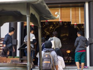 Visitors ascend the steps to the Amida-do hall to pray for protection from evil
