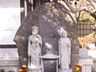 Two stone deities stand before the temple gates, ready to hear your prayers