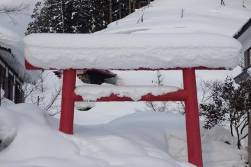 A half-buried red torii shows the depth of the snowfall here.