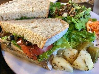 Sandwich gà ướp thảo mộc và salad.