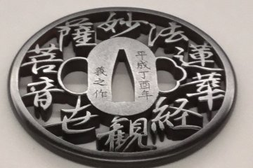 A tsuba with a verse from Buddhist scripture