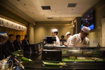 Chefs preparing the sushi behind the counter