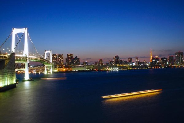 Trails of ships passing below the rainbow bridge with Tokyo Tower in the distance