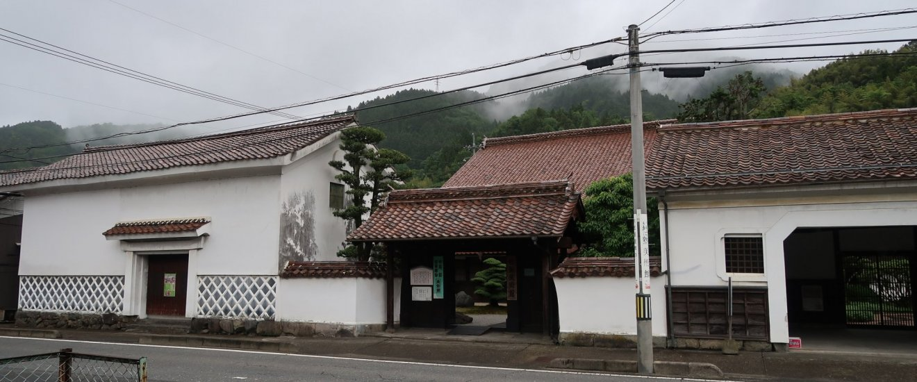 The front gate of the Morijuku Art Gallery with some rice granaries on either side of the gate