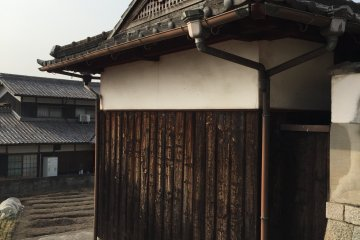 An old structure with scorched cedar panels in Konko-cho