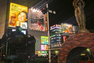 신바시는 불빛으로 가득 차 있고 금요일 밤 역 앞에 많은 사람들을 볼 수 있을 것이다