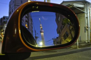 Reflection in a car's side mirror in the bylanes of Oshiage