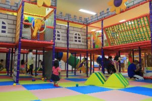There is one toddler play area and three larger play areas like this one that each have an open center court surrounded by various play stations and topped by a second level of catwalks full of surprises