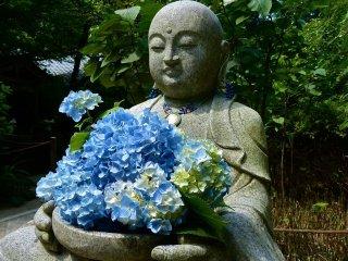 Jizo statue holding blue hydrangea flowers