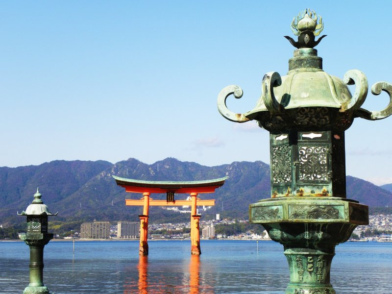 Bronze dai-toro platform lanterns with floating torii gate and mountains in the background. The lantern on the left is actually in between two lanterns. Did you notice the difference in metalwork on each lantern's head?