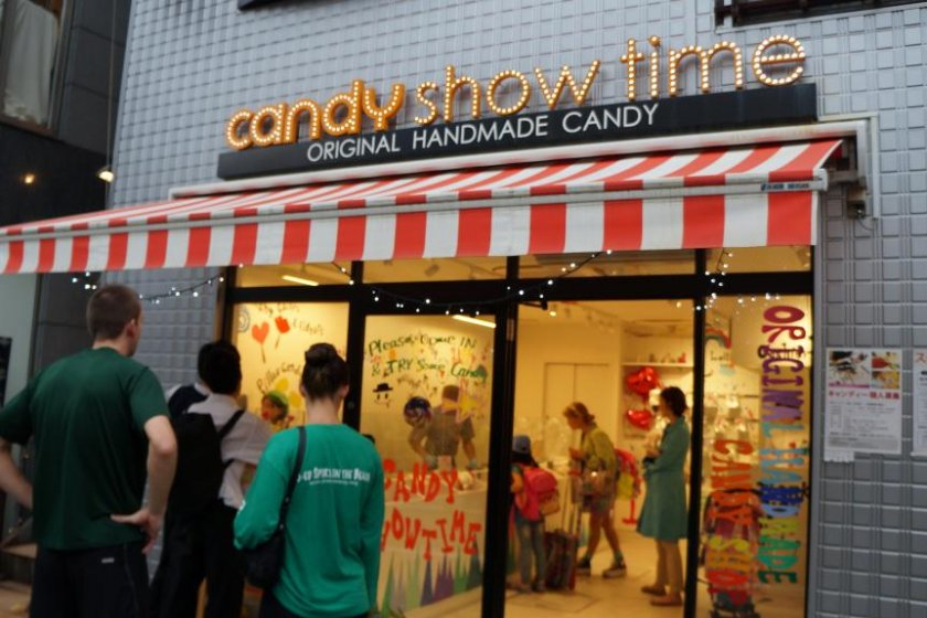 Pedestrians stop to watch the candy-making process, sometimes for ten or even twenty minutes