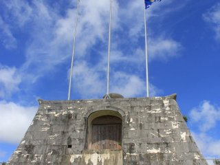 The stadium's flag poles rest upon a stone gate inspired by the Sonohyan Utaki UNESCO World Heritage Site in Naha