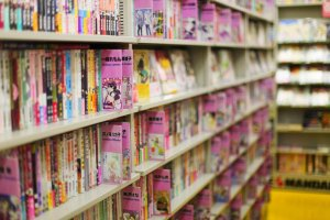 Shelves lined with pink manga and dōjinshi