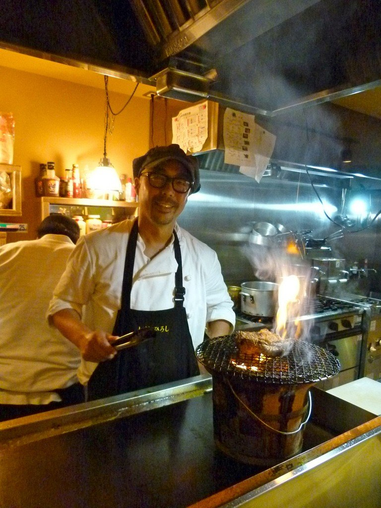 Chef grilling steaks on a hibatchi stove
