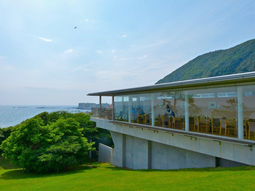 Quán cà phê nằm trong một căn phòng dài, được bao phủ bằng kính, hướng nhìn ra biển xanh tuyệt đẹp