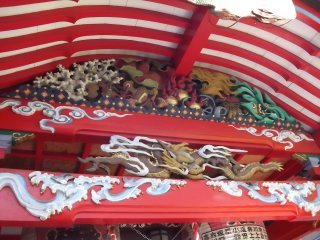 Brightly painted carvings under the eaves of the prayer hall