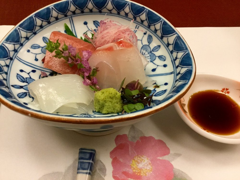 Everything on this plate is edible. The decorative flowers enhance the freshness  sashimi.