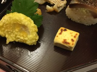 The menu changes with the season. This is an autumn themed dish featuring a deep fried lotus root and behind the leaf, a sweet pumpkin. The roasted square block is a tofu product that tastes like cheese.