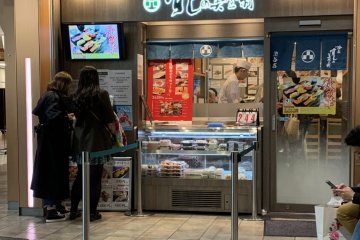 The front of Sushi no Midori.  Note the two customers at the left where the ticketing machine is located to get your serving number