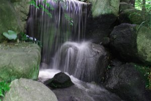 The rushing waters of the waterfall complement the harmony of the garden.