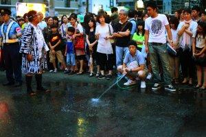 ฝูงชนช่วยทำให้ถนนเปียกเพื่อเตรียมการสำหรับขบวนแห่