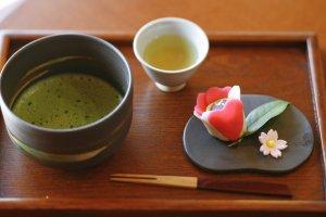 Thé vert Matcha avec une pâtisserie wagashi en forme de fleur de camélia.
